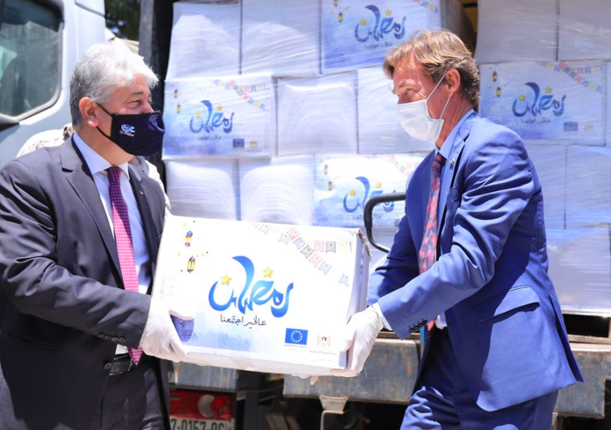 EU representative to the Palestinians Sven Kühn von Burgsdorff, right, hands more than 800 food packages to the PA's social development minister to be distributed to poor Palestinian families