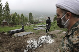 A woman wearing mask and gloves prays over the grave of her mother who died from COVID-19 at a cemetery on the outskirts of Babol, northern Iran