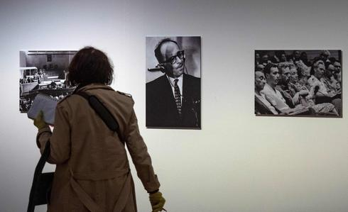 A visitor walks past a portrait of Nazi war criminal Adolf Eichmann (C) during his trial in Jerusalem at an exhibition on German-American philosopher and political theorist Hannah Arendt