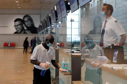 An employee disinfects surfaces at a counter in the departures terminal at Ben Gurion Airport