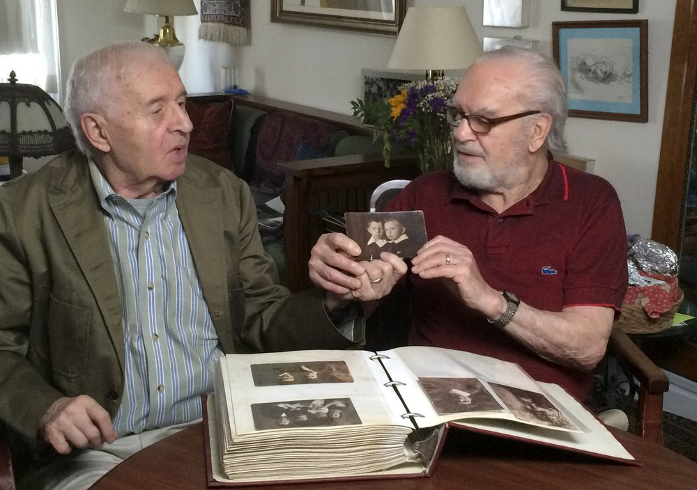 Brothers Alexander Feingold, left, and Joseph Feingold look at photo of themselves as boys in Joseph's apartment in New York