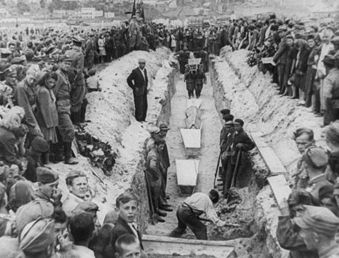 In this July 1946 file photo mourners crowd around long a narrow trench as coffins of victims of an anti-Semitic massacre are placed in a common grave following mass burial service, in Kielce, Poland. The July 4,1946, massacre killed 42 people, most of them Jews, and wounded over 80