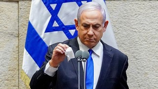 Prime Minister Benjamin Netanyahu disinfects the microphone before addressing the Knesset, May 2020