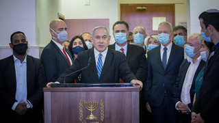 Flanked by Likud ministers and MKs, Benjamin Netanyahu attacks the judicial system at the start of his criminal trial in Jerusalem, May 2020
