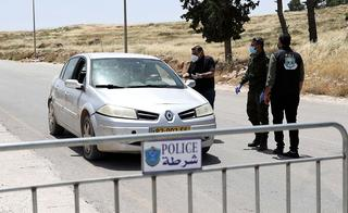 Palestinian police officers man a roadblock north of the West Bank city of Hebron  during the virus outbreak