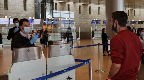 A masked official examines the passport of a traveler at a near-deserted Ben-Gurion Airport during the pandemic