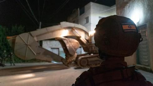 An IDF soldier watches a bulldozer about to demolish the home of Omar Amin Abu Laila in the Zawiya neighborhood of Nablus at dawn, April 24, 2019