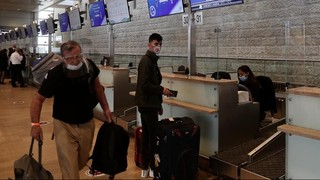 Passengers and staff wear masks at Ben-Gurion International Airport, Israel's primary port of entry