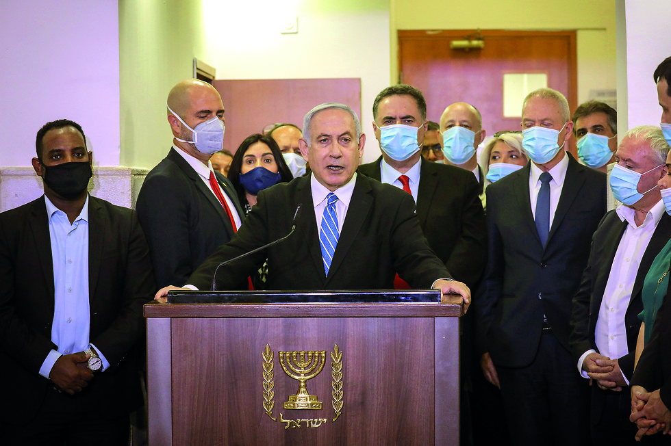 Prime Minister Benjamin Netanyahu, flanked by lawmakers from his Likud party, gives a statement shortly before the opening hearing of his corruption trial
