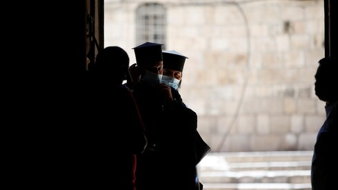 Members of the clergy wear masks as they stand near the entrance of Church of the Holy Sepulchre in Jerusalem