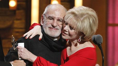 """Larry Kramer, left, and Daryl Roth embracing after they won the Tony Award for Best Revival of a Play for """"The Normal Heart"""" during the 65th annual Tony Awards in New York"""