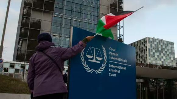 A demonstrator poses with a Palestinian flag outside the International Criminal Court