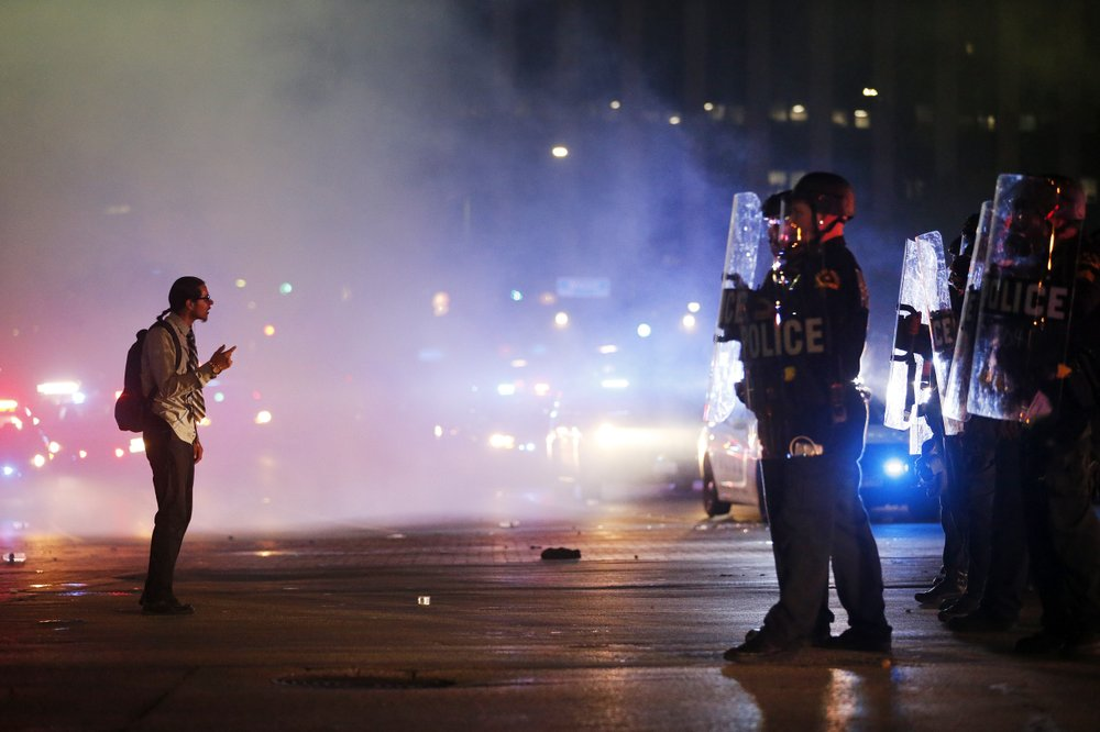 A protestor stands in the middle of the tear gas confronting tactical officers at the intersection of Young St. and S. Griffin St. in downtown Dallas
