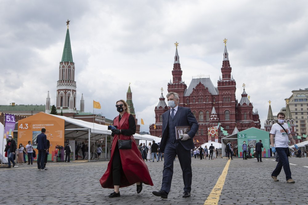 People wearing face masks to protect against coronavirus walk an outdoor book market set up in Red Square with a Historical museum in the background in Moscow, Russia
