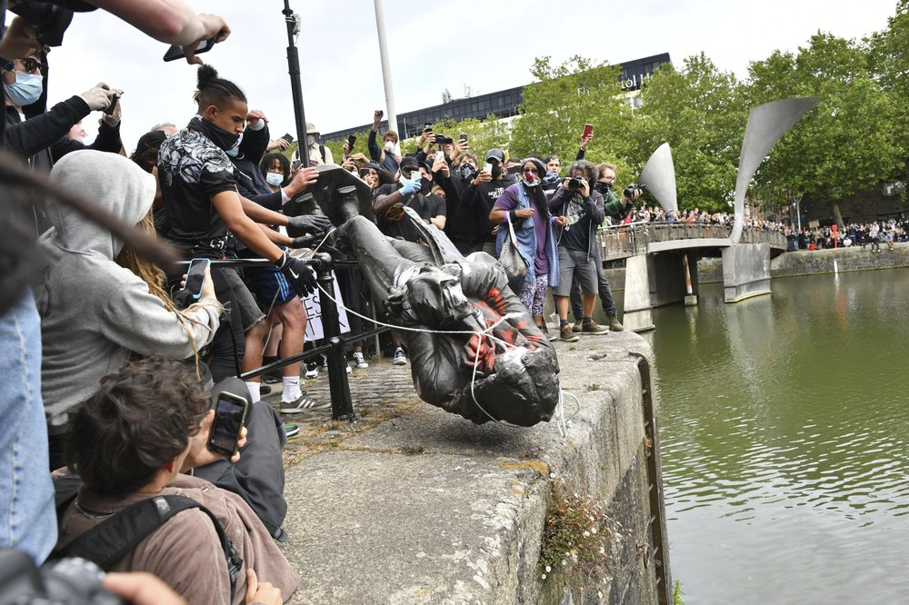 Protesters throw a statue of slave trader Edward Colston into Bristol harbor, during a Black Lives Matter protest rally, in Bristol, England