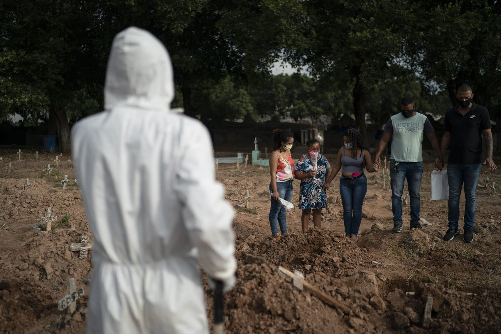 Relatives attend the burial of 57-year-old Paulo Jose da Silva, who died from the new coronavirus, in Rio de Janeiro, Brazil