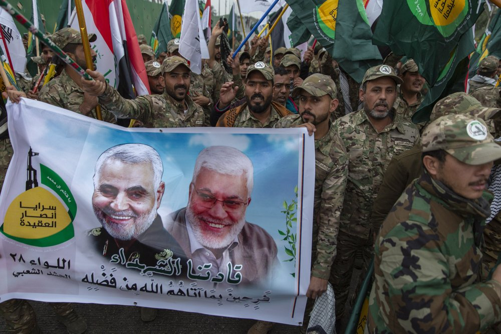 Iraqi militiamen march and chant anti U.S. slogans while carrying a picture of Soleimani, left and al-Muhandis, with Arabic that reads 'our martyr leaders'