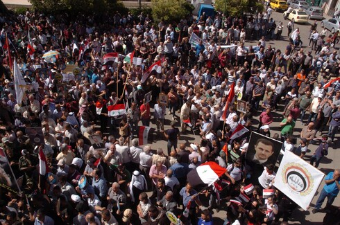 Supporters of Syria's President Bashar al-Assad carry his pictures and flags during a demonstration in the mainly Druze city of Sweida, Syria