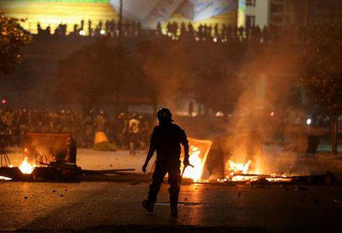 A member of the Lebanese riot police walks near burning fire during a protest against the fall in pound currency and mounting economic hardship, in Beirut, Lebanon