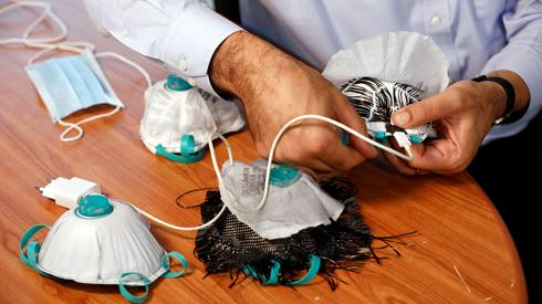 An Israeli researcher, part of a team which say they have invented a reusable face mask that can disinfect itself and kill the coronavirus disease (COVID-19), takes part in a demonstration
