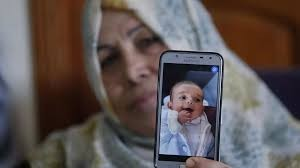 The grandmother of nine months old Palestinian baby Omar Yagi displays a picture