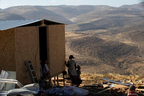 A settler and children stand next to a temporary structure in the West Bank outpost of Maoz Ester