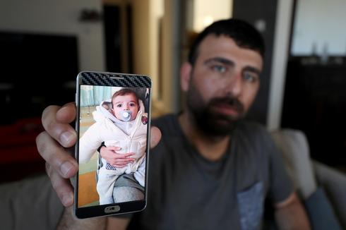 Ahmed Yaghi, the father of Palestinian infant Omar, who died of illness, shows his picture on his mobile phone in the central Gaza Strip