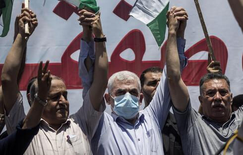 Hamas leader in the Gaza Strip, Yahya Sinwar, center, attends a demonstration against Israeli plans for the annexation of parts of the West Bank, in Gaza City, July 1, 2020