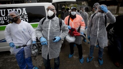 Palestinian workers get ready to disinfect mosques and churches in the West Bank city of Ramallah