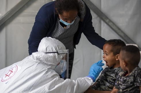 A child is tested for coronavirus by a healthcare worker at testing center for migrants in Tel Aviv