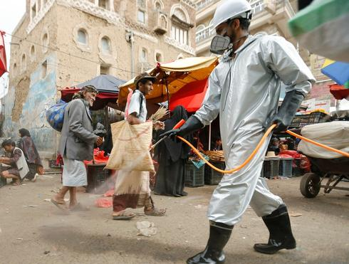 A health worker disinfects a market amid concerns of the spread of COVID-19, in Sana'a, Yemen