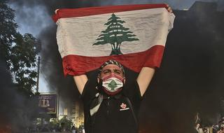 A protester holds up the Lebanese flag during a demonstration in Beirut, June 2020