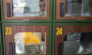 A customer reads the menu at Go noodles, where her order will be served in one of the glass-paned lockers seen behind her