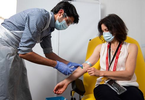 In this handout photo released by the University of Oxford, a doctor takes blood samples for use in a coronavirus vaccine trial in Oxford, England, on June 25, 2020