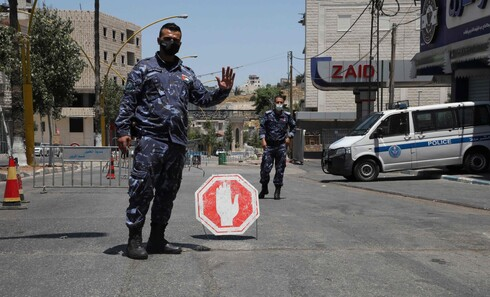 A member of the Palestinian security forces controls the cars entering the West Bank town of Hebron
