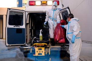 EMT's cleanse their materials outside Memorial West Hospital where coronavirus disease patients are treated, in Pembroke Pines, Florida