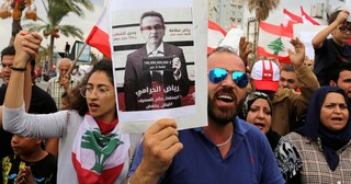 Demonstrators carry Lebanese flags and a banner depicting Lebanon's Central Bank Governor Riad Salameh, as they head towards the central bank building during an anti-government protest