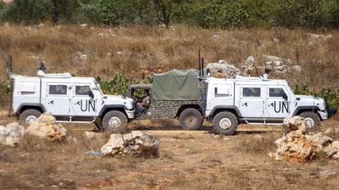 Lebanese soldiers on patrol drive by UN vehicles on the border with Israel, July 28, 2020