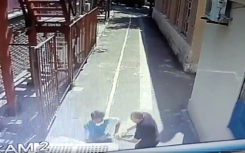 Screen capture from video of a security guard outside a synagogue in Ukraine struggling with an ax-wielding attacker