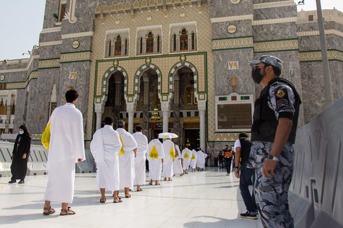 Security personnel stand near pilgrims maintaining social distancing outside as they enter the Grand Mosque in Mecca on the first day of Hajj,  July 29, 2020