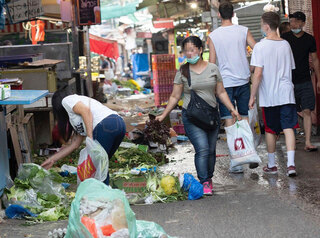 A woman searches the garbage for food at an Israeli market during the coronavirus pandemic