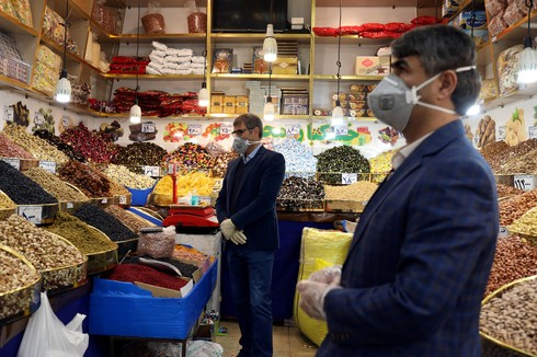 Men wear protective face masks and gloves in a food shop in Tehran following the outbreak of coronavirus