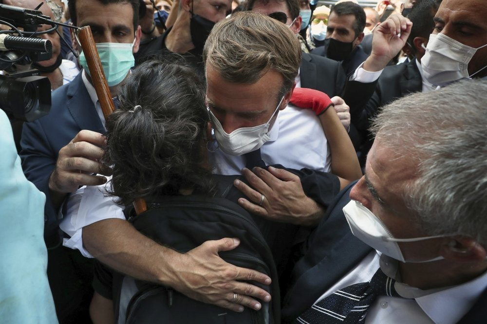 French President Emmanuel Macron, hugs a woman as he visits the Gemayzeh neighborhood, which suffered extensive damage from an explosion on Tuesday that hit the seaport of Beirut, Lebanon