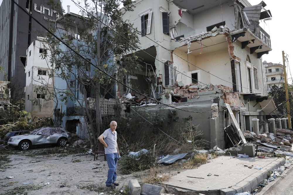 A Lebanese man stands next to his damaged house near the scene where an explosion hit on Tuesday the seaport of Beirut, Lebanon