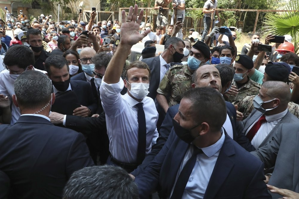 French President Emmanuel Macron, center, gestures as he visits the Gemayzeh neighborhood, which suffered extensive damage from an explosion on Tuesday that hit the seaport of Beirut, Lebanon