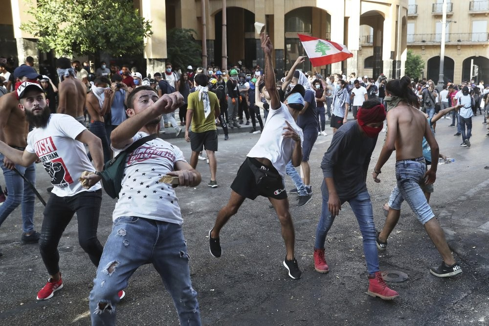 Protesters throw stones against the Lebanese riot police, during anti-government protest following Tuesday's massive explosion which devastated Beirut, Lebanon