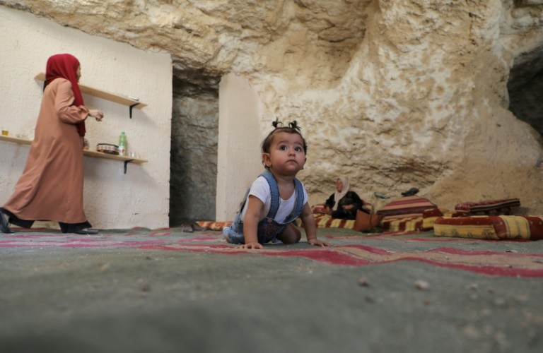 The daughter of Ahmed Amarneh crawls on a carpet at his home built in a cave, in the village of Farasin, west of Jenin, in the northern West Bank