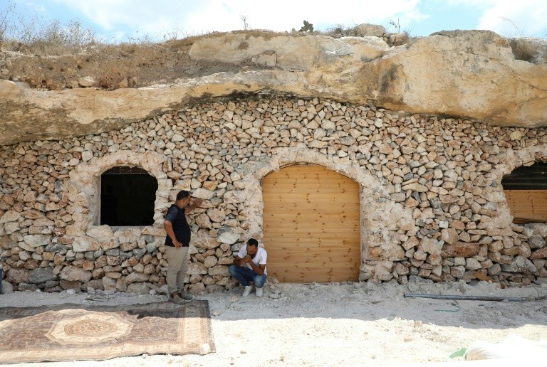 Ahmed Amarneh and a neighbor chat outside his home, built in a cave in the village of Farasin, west of Jenin, in the northern West Bank