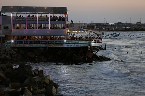 Palestinians sit at a beachfront cafe in Gaza City
