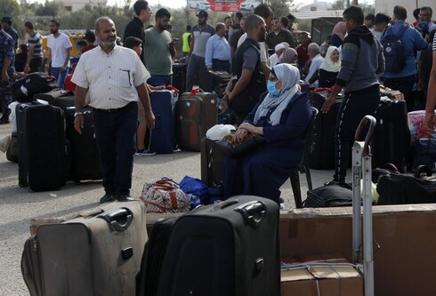 Passengers sit next to their luggage as they wait to cross the border to the Egyptian side of Rafah crossing, in Rafah, Gaza Strip